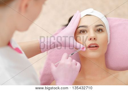 Beautiful woman gets injection in her lips.