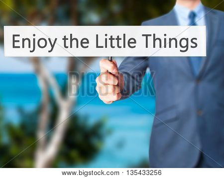Enjoy The Little Things - Businessman Hand Holding Sign