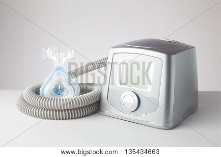 Sleep Apnea CPAP machine with hose and head hear mask on white table