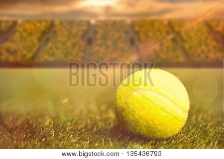 Close up of tennis ball on the grass against terraces with spectators