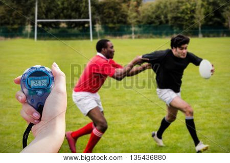 Close up of a hand holding a timer during a rugby match