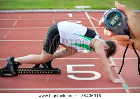 Composite image of a hand holding a timer against athletic man on the starting line putting his foot in the starting block