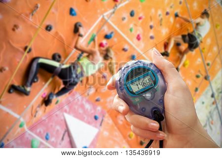 Composite image of a hand holding a timer against fit couple rock climbing indoors