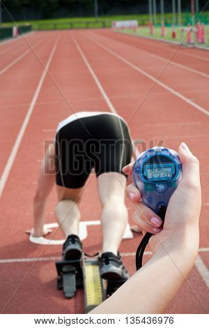 Close-up of a woman holding a chronometer to measure performance against sporty man waiting in starting block