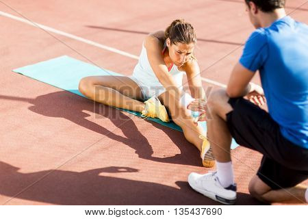 Woman training with personal trainer outdoor on a sunny day