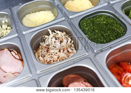Sandwich bar salads choice in metal containers. Different fillings - chicken meat, sliced ham, tomatoes, fresh herbs for preparing fast food take away in cafe. Vendor's equipment for street meal.