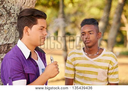 Youth culture young people group of male friends multi-ethnic teens outdoors multiracial boys together in park. Kids smoking electronic cigarette e-cig smokers. Health problems social issues
