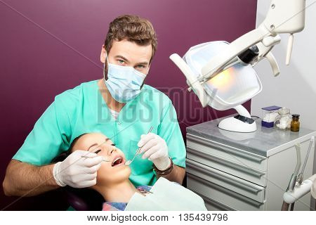Male Dentist Examines Mouth Of Woman On The Dentist's Chair