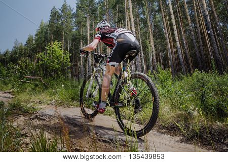 Kyshtym Russia - June 16 2016: male cyclist riding a bike on forest trail during Championship of Russia on mountain bike