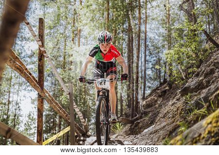 Kyshtym Russia - June 16 2016: girl athlete cyclist rides down mountain a wooden bridge during Championship of Russia on mountain bike