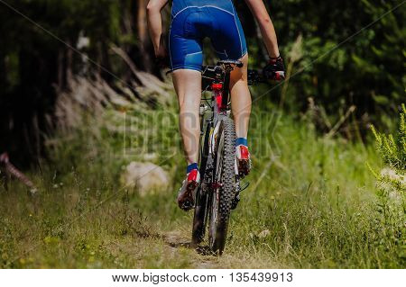 male cyclist riding a bike on forest trail