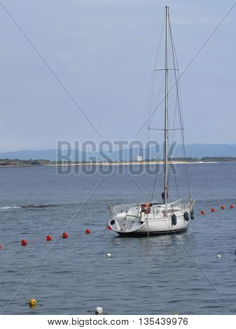 Single sailboat lies at anchor in a harbor waiting for the wind to shift . Tuscany Italy