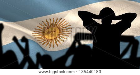 Silhouettes of football supporters against digitally generated argentina national flag