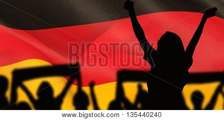 Silhouettes of football supporters against digitally generated german national flag