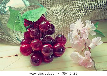 sacks and grapes and pink flower on wood background.effcet vintage style