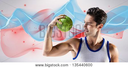 Happy male athlete holding a ball against blue wave