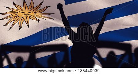 Silhouettes of football supporters against digitally generated uruguay national flag