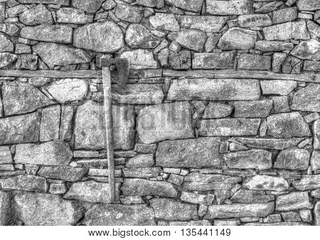 Stylish stone wall background and axe in black and white