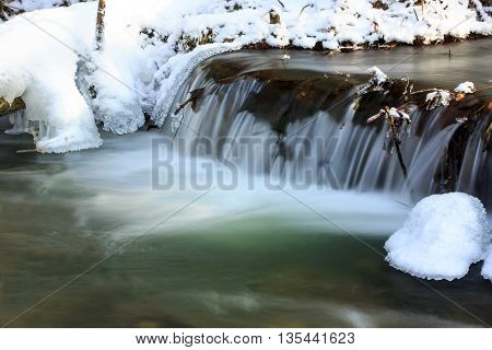 small waterfall on mountain river in winter time