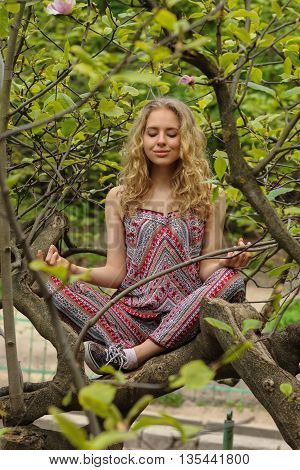 The girl meditates sitting on magnolia tree in the garden lotus pose