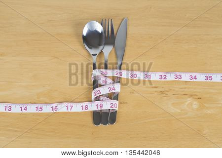 Healthy eating concept Measuring tape around culery