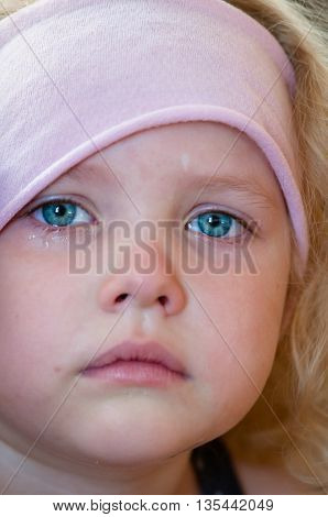 Caucasian little girl with blue eyes curly blonde in a pink hat crying tears running down the face close-up