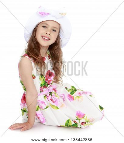 Charming little girl in a smart white dress with roses and a white cap , sitting on the floor - Isolated on white background