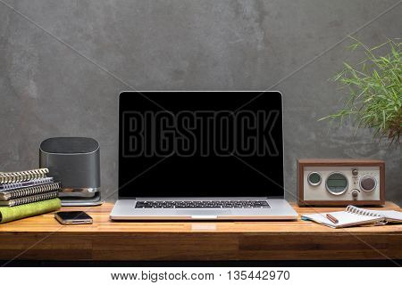 laptop smart phone on wooden worktable concrete wall background