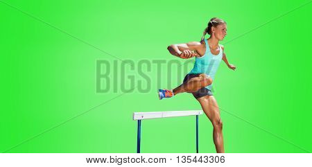 Sportswoman practising the hurdles against green background