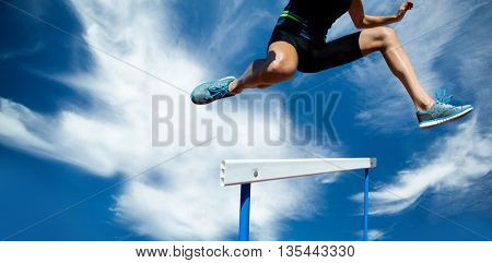 Athletic woman doing show jumping against blue sky with clouds