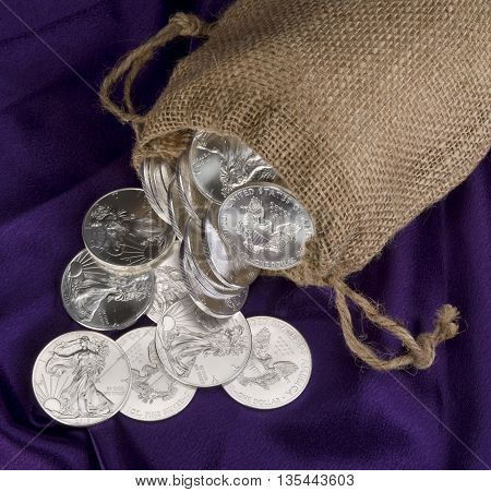 Burlap sack full  of silver eagle dollars.