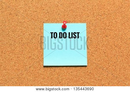 Blue sticky note on cork board with push red pin.