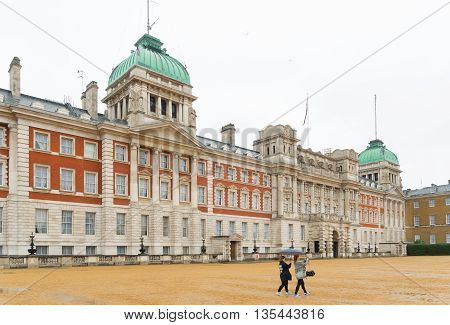 LONDON ENGLAND - OCTOBER 21, 2015: Two unknown tourists in front of the Whitehall palace. The Palace of Whitehall (or Palace of White Hall) was the main residence of the English monarchs in London from 1530 until 1698
