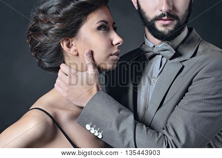 Portrait of beautiful lady with handsome guy in suit. Young couple is hugging each other. Girl and boy with attractive faces indoors in passionate pose. Beauty woman with hairstyle. Man with a beard