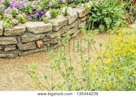 Fragment of decorative alpine slide with a retaining wall and flowers in the summer garden. Selective focus