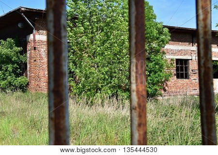 Old abandoned building in the foreground grids gateway