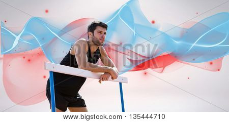 Athletic man pressed on a hurdle posing against blue wave