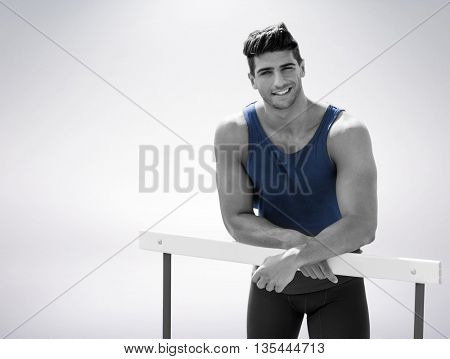 Portrait of sportsman is smiling and posing on a hurdle against grey background