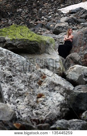 blond woman in black dress among the huge stones on the glacier. Mestia, Georgia
