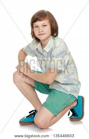 A handsome young man in turquoise shorts and a shirt with short sleeves-Isolated on white background