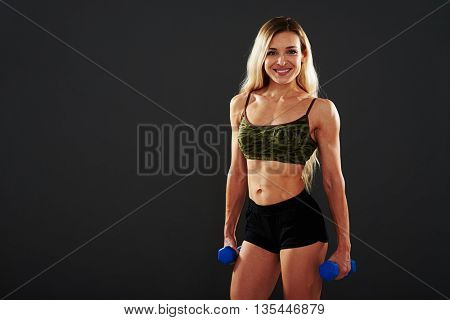 Attractive athletic woman with well trained muscular body is standing with dumbbells in her hands on black background