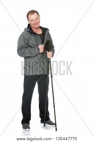 A 50 year old man in a track suit , relies on sticks for Nordic walking-Isolated on white background