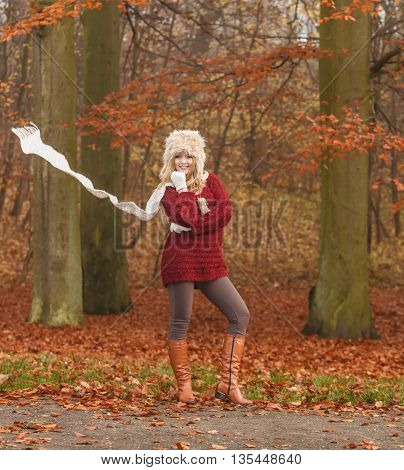 Fashion woman with flying scarf in windy fall autumn park forest against blowing wind. Young girl posing in fur cap and sweater having fun outdoor.