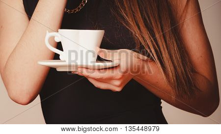 Elegant part body woman in black holding coffee tea beverage in white heart shaped cup mug on saucer plate.