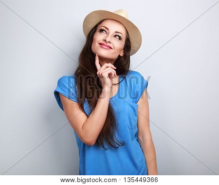 Happy Casual Friendly Woman In Summer Hat Thinking And Looking Up On Blue Background