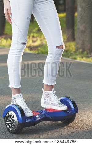 Girl using a self-balancing two-wheeled board. The gyroscope based dual wheel electric scooter is also called a smart balance wheel. Feet on hover board scooter