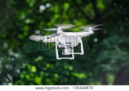 Drone with camera flying on a background of trees