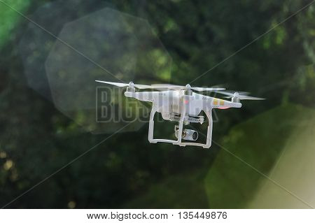 Drone with professional camera flies against background of trees and sun glare