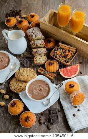 Two cups of fresh hot cocoa or hot chocolate with muffins juice and raisin cake on wooden background top view