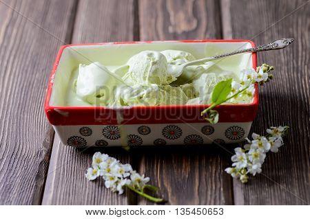 Pistachio ice cream in a big container bird cherry flowers